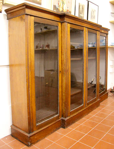 A late Victorian walnut veneered breakfront bookcase,
