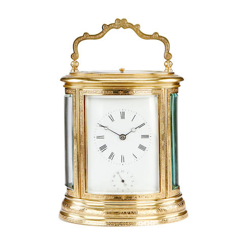 A third quarter 19th century French oval brass carriage clock with alarm and repeat