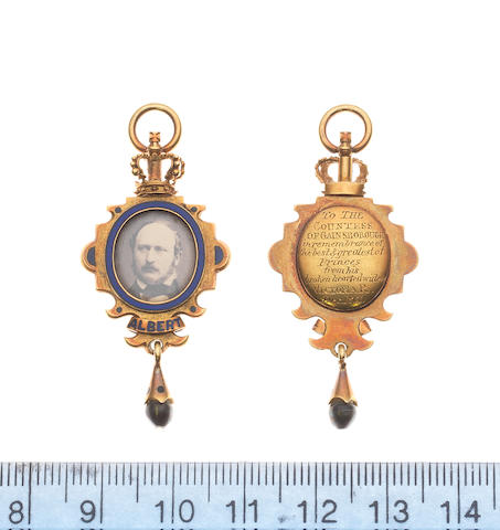 Victorian Memorial Pendant, in gold with blue enamel containing a photograph of Prince Albert, a scroll is below with an inscription, at the top is a crown and at the bottom a pendant.