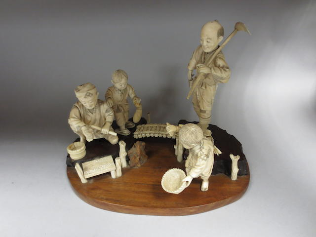 A late 19th century Japanese ivory figure group comprising two men and two boys harvesting fruit and vegetables. On a wooden base. 27cm wide x 21cm high overall.