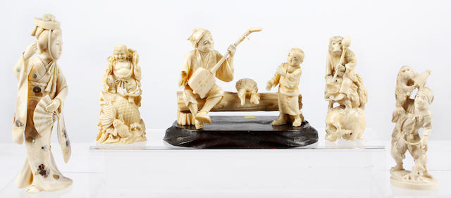 A Japanese meji period carved ivory okimonoDepicting Ebisu standing on a fish, 10cm high, a further carving of a monkey on a toad, 11cm, another figure with monkey, 12.5cm, a further figure group and a Shibayama decorated figure (5)