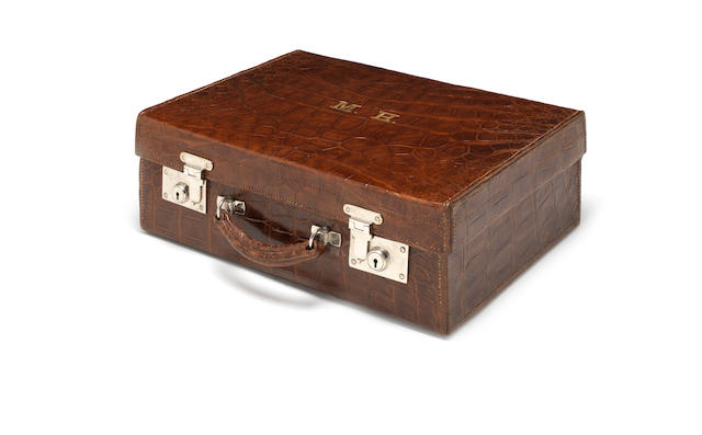 A  brown crocodile leather  vanity case, initialled 'MH', with tortoiseshell mounted part dressing table set the mounts by Charles Henry Dumenil, London 1905-1907  (10)