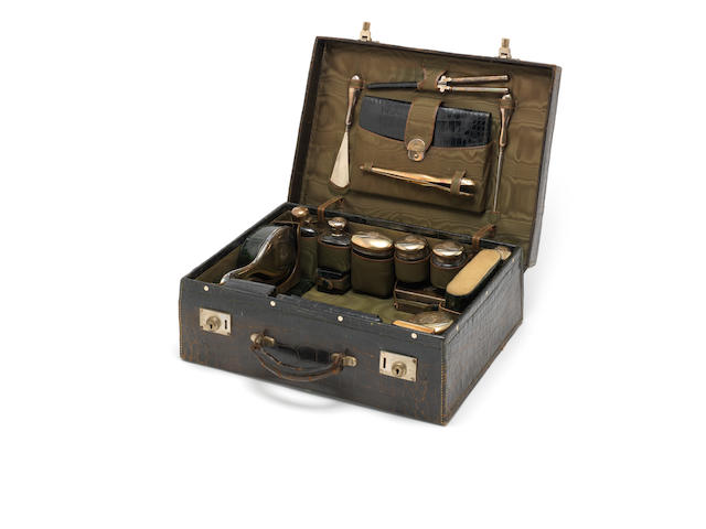 An Edwardian crocodile leather case, initialled 'A.A.W', containing a silver-mounted gentleman's dressing table set the silver mounts by Samuel Summers Drew & Ernest Drew, London 1904, retailed by Drew & Sons, Piccadilly, London