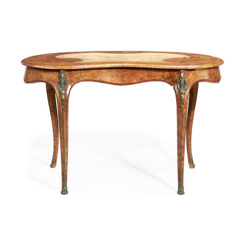 An early Victorian brass mounted walnut and tulipwood banded kidney-shaped writing table in the Louis XV style