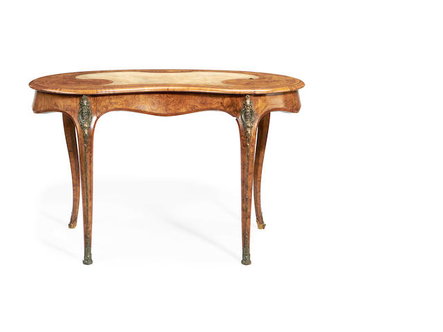 An early Victorian brass mounted walnut and tulipwood banded kidney shaped writing table in the Louis XV style