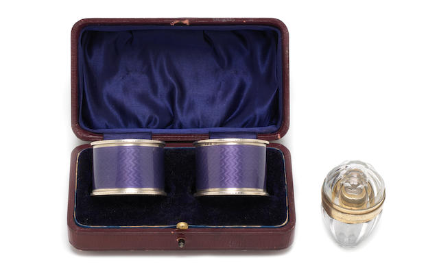 A cased pair of continental silver and enamel napkin rings with import marks for George Stockwell, London 1928; together with a 19th century French glass and silver-gilt mounted scent bottle  (3)