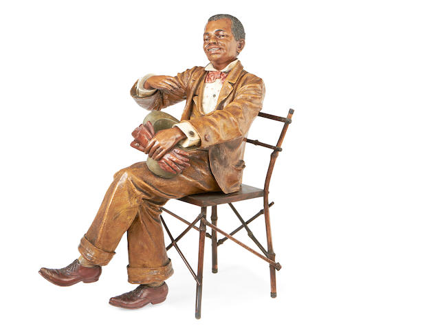An early 20th century Goldscheider style terracotta figure of a seated man