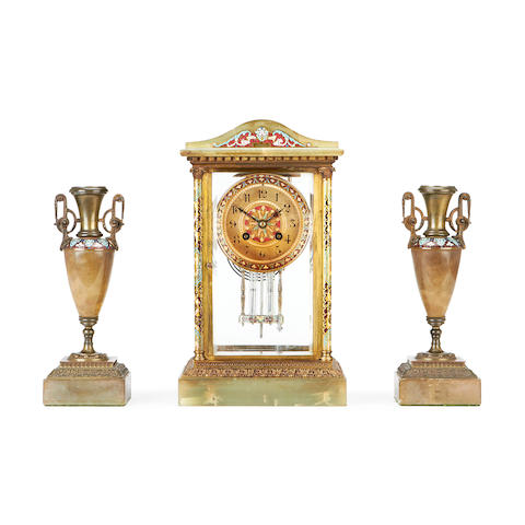 A late 19th century onyx, gilt metal and champlevé enamel four glass mantel clock garniture