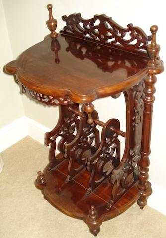 A reproduction mahogany Canterbury, shaped two tier with pierced dividers on turned legs, 92cm high.