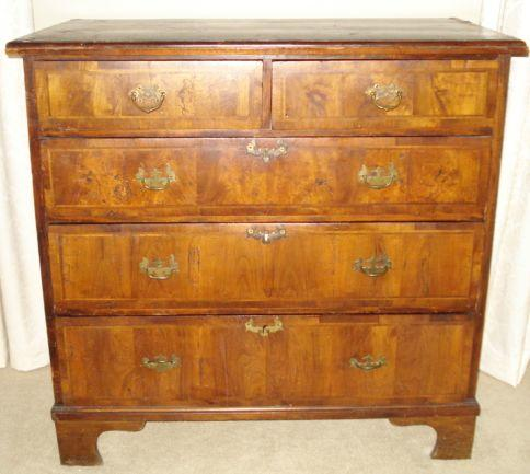 An 18th Century crossbanded walnut chest, of two short and three long drawers on shaped bracket feet, 95cm.