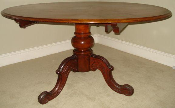 Victorian mahogany breakfront table, the oval moulded edge top on baluster column and three carved cabriole legs, 135 x 115cm.