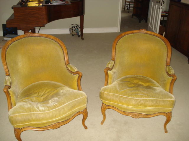 A pair of carved back framed bergeres, with moulded frames on carved cabriole legs having loose feather cushions.