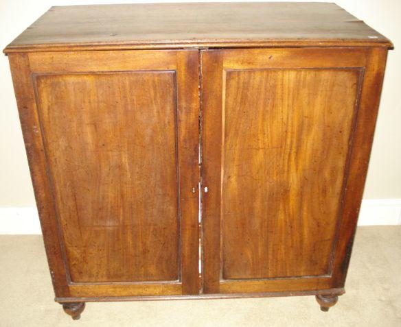 A 19th Century mahogany press cupboard, the double door enclosing linen slides on turned legs, 102cm.