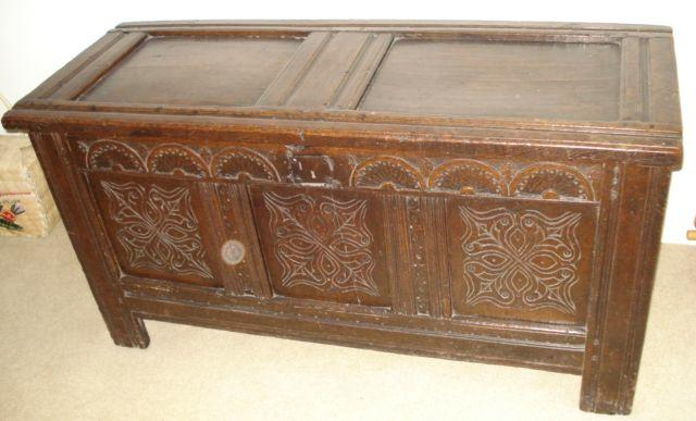 A 19th/18th Century oak coffer, the lift lid over a carved triple panel front, sides to stile feet, 126cm.