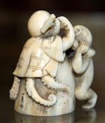 An ivory netsuke of a monkey and octopus