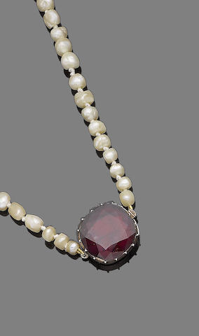 A pearl necklace with garnet clasp