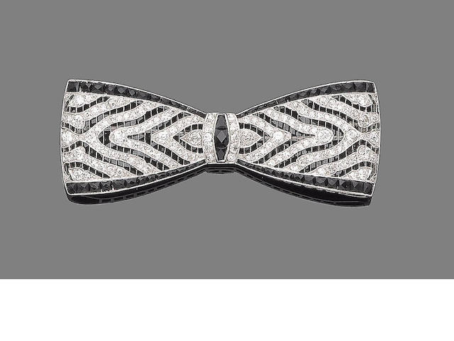 An onyx and diamond bow brooch