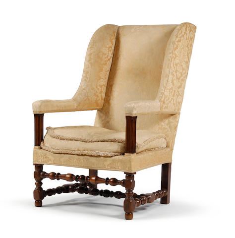 A walnut framed upholstered wing armchair