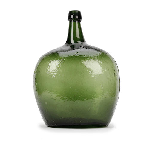 A large mould-blown green glass carboy