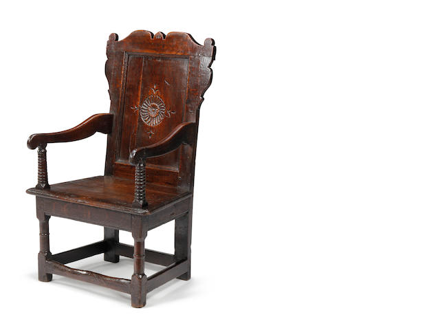 A Charles II oak panel back open armchair Circa 1660