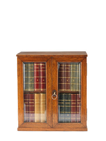 An early 20th century oak humidor in the form of a small bookcase