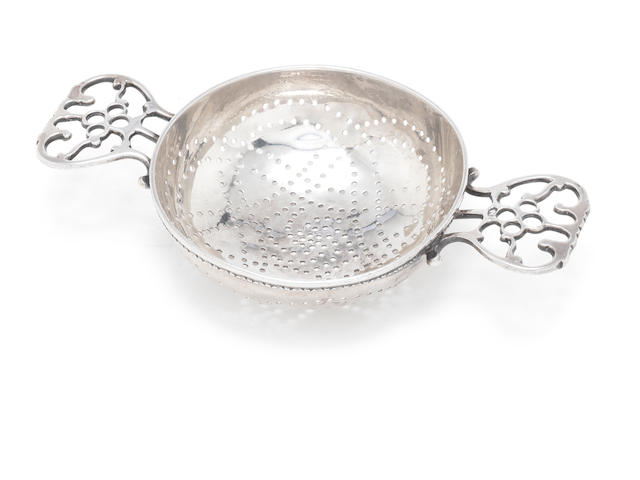 "An unusual 19th century Canadian silver two-handled lemon strainer stamped pseudo marks depicting a duty mark, gothic E and lion passant,  also incuse stamped ""STERLING"" on one handle,"