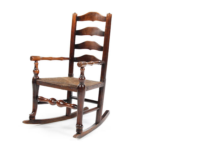 A 19th century child's graduated fruitwood ladderback rocking chair