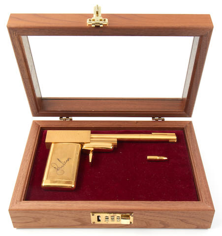 James Bond - The Man With The Golden Gun: A replica gun autographed by Roger Moore,