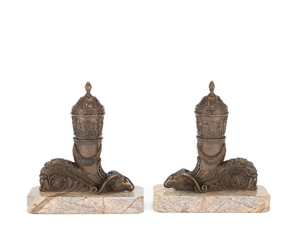 A pair of bronze lidded urns in the style of Thomas Messenger