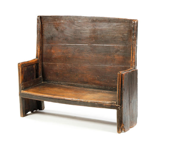 An 18th century elm and oak primitive boarded settle.