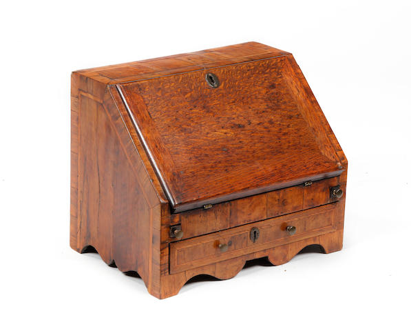 An early 18th century style walnut and oak miniature bureau