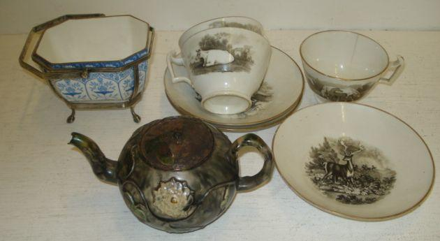A mid 18th Century Staffordshire globular shape teapot, circular 1755 with crabstock handle, the body with mottled colouring and applied with moulded scrolling flowering branches, tin cover, 16cm, three early 19th Century bat printed tea cups and saucers and a Wedgwood sugar basket in electroplated frame.