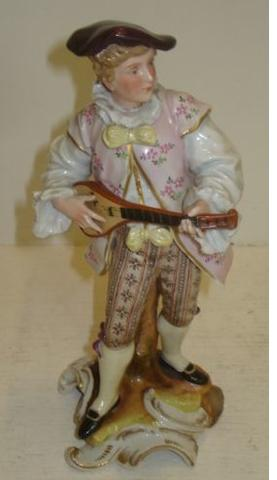 A Sitzendorf porcelain figure of a musician, playing a mandolin, gilt scrollwork base, 25cm.