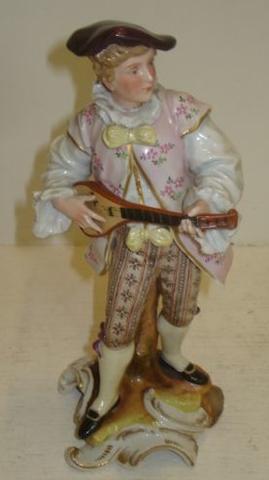 A Sitzendorf porcelain figure of a musician, playing a mandolin, gilt scrollwork base, 25cm.