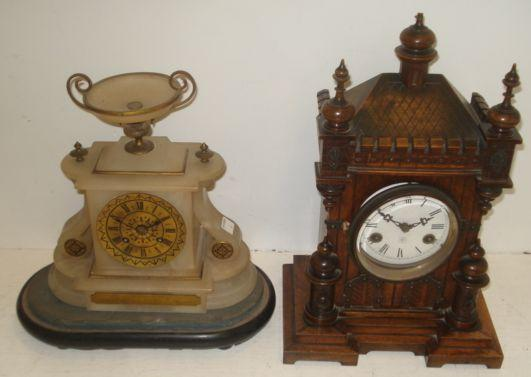 A Victorian alabaster gilt metal mounted and black enamelled mantel clock, surmounted by an urn, the 8 day movement striking on a bell, 25cm, with ebonised plinth and Presentation Plaque inscribed and dated 1868 and a German late 19th Century mantel clock, in a carved walnut architectural style case, the 8 day movement striking on a gong, both with keys.