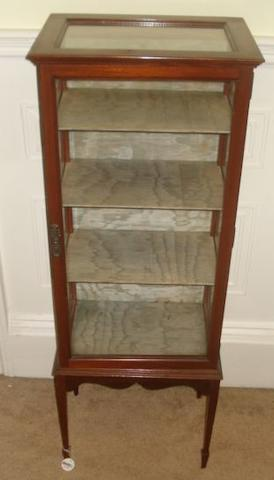 An Edwardian upright display case, the top and three glazed sides enclosing shelves, shaped apron and tapered legs to spade feet.