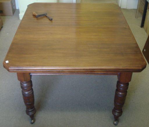An Edwardian walnut cut corner rectangular dining table and leaf, on ring turned legs, 174 max x 102cm.