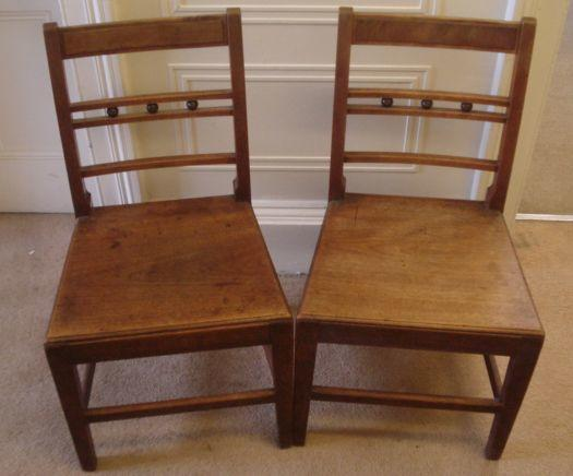 A set of six 19th Century fruitwood solid seat dining chairs, each with horizontal sphere set rails and a similar elbow chair with shaped back rail.