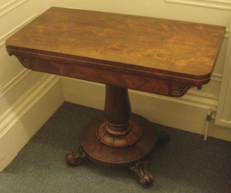 A Victorian rosewood card table, the folding top over a scroll carved frieze on baluster column on a circular base, 91cm.