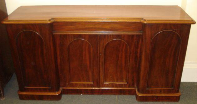 A Victorian mahogany inverted breakfront sideboard, the moulded edge top above a centre frieze drawer with a cupboard under and flanking cupboards enclosed by arched sunk panel doors, on a plinth base, 184cm.