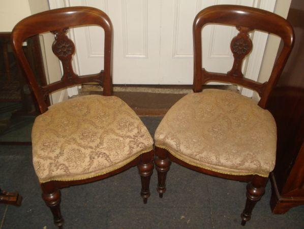 A set of four Victorian mahogany dining chairs, with open backs and carved splats, stuff over seats, on turned and fluted tapering legs.