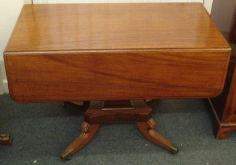 A late Regency mahogany breakfast table, the rectangular top with hinged drop leaves, end drawer, on a tapering square pillar, the concave platform on a quadripartite base, 104cm.