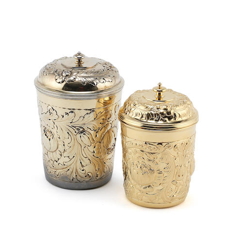 A late Victorian silver-gilt covered beaker by William Comyns, London 1894 with another similar covered beaker, Harold Child, London 1901 (2)