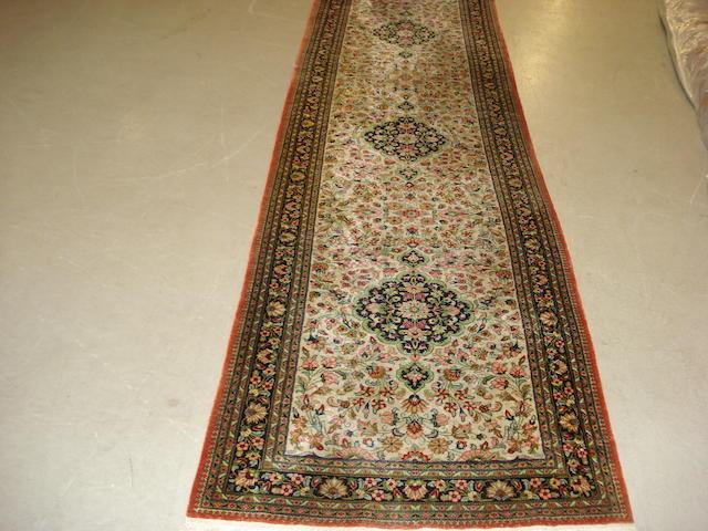 A silk Ghom runner, Central Persia, 407cm x 91cm