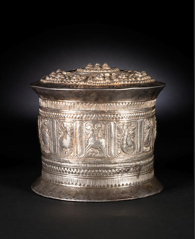 A Tibetan or Himalayan white metal cylindrical box and cover