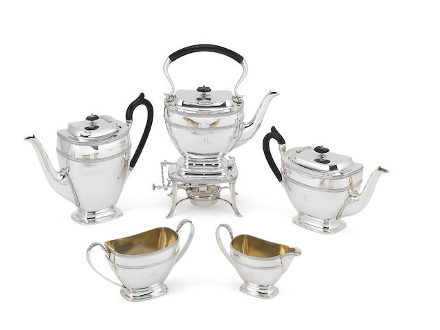 A five-piece silver tea service with kettle on stand
