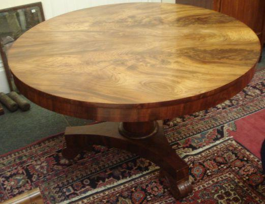 A William IV mahogany dining table, the well figured circular tilt-top on a cylindrical tapering pillar, the concave sided platform base on scroll carved feet and castors, 121cm.
