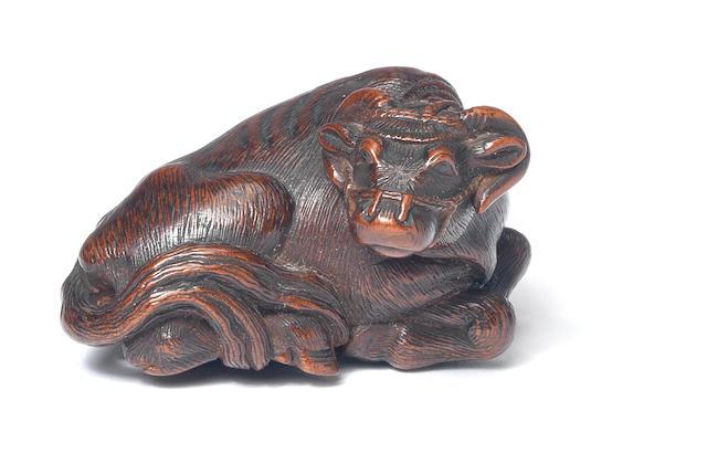 A wood netsuke of a recumbent ox By Matsuda Sukenaga, Takayama, Hida province, 19th century