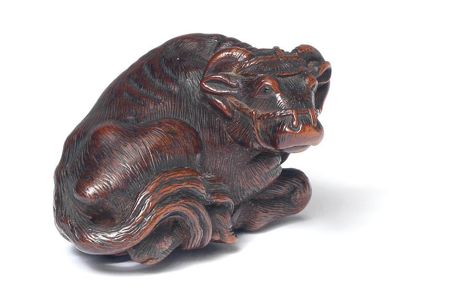 A wood netsuke of a recumbent ox By Matsuda Sukenaga (1810-1871), Takayama, Hida Province, 19th century