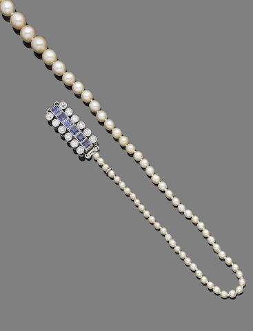 A single-strand pearl necklace with a sapphire and diamond clasp